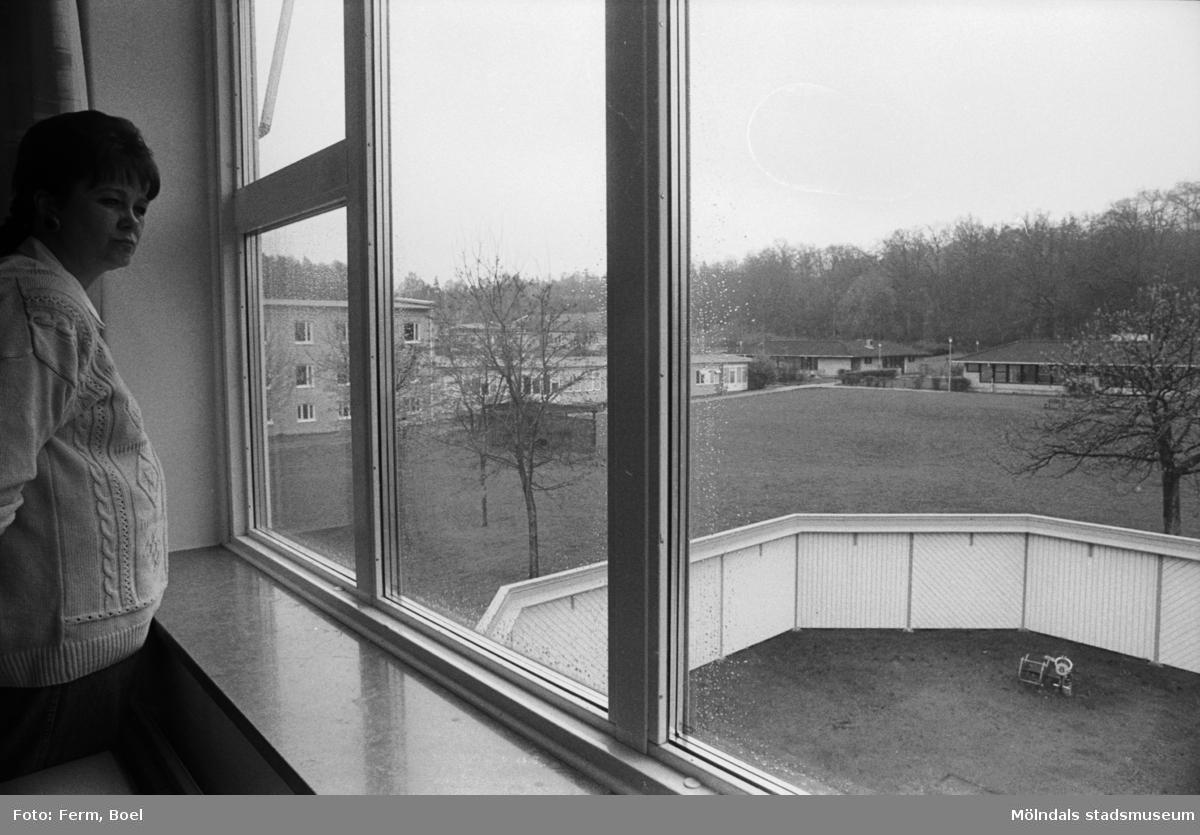 Dokumentation av Sagåsens flyktingförläggning 1992. En gravid kvinna i vit tröja, står och tittar ut genom ett fönster mot förläggningens lekplats.