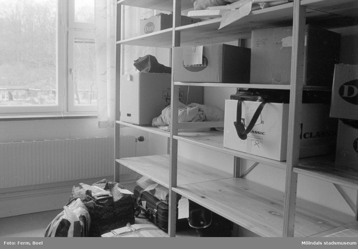 Dokumentation av Sagåsens flyktingförläggning 1992. Ett rum med tre ihopmonterade lagerhyllor som innehåller kartonger, resväska och kassar. I bakgrunden finns fönster.