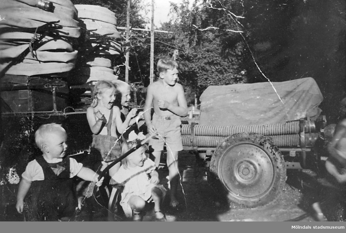 Barnen står vid brandspruta och slangar utanför Lindome brandstation 1950. Den minste är Bengt Karlsson. Vid brandbilen står Monika Ahlgren, Kent Andersson, Yngve Thainsson samt Tiina Mahlakaaska.
