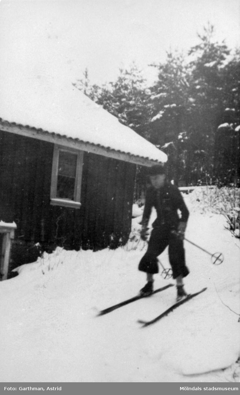 Okänd man åker skidor utför en sluttning invid ett hus i Fjärås Bräcka, 1940-tal.