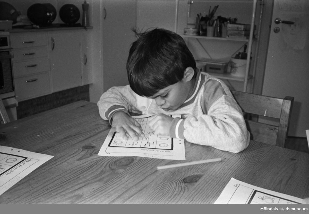 En pojke sitter inomhus vid ett bord och fyller i figurer på ett papper. Katrinebergs daghem, 1992-93.
