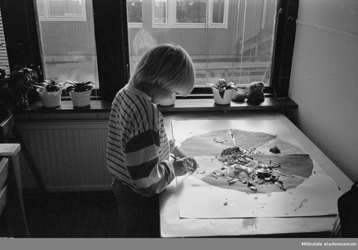 """En pojke står vid ett bord som är uppställt brevid ett fönster. På bordet ligger en teckning som är målat i olika kulörer som en delad apelsin. Barnet målar med en pensel i en av """"klyftorna"""". Katrinebergs daghem, 1992."""