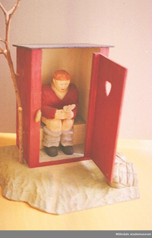 """Ett rött utedass med öppen dörr. Därinne sitter en rödhårig person på toaletten och läser i en tidning. Den öppna dörren är försedd med ett hjärta. Utanför står ett litet träd. Harry Bergmans """"gubbar"""" (träfigurer). Liknande foto som 1994_0964."""