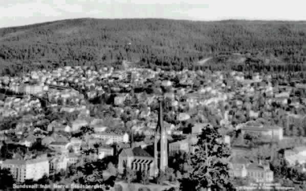 """Stadsvy över Sundsvall. Till vänster en del av Stenstaden, till höger Västermalm med Gustav Adolfskyrkan i förgrunden. Text till bild """"Sundsvall från Norra Stadsberget""""."""