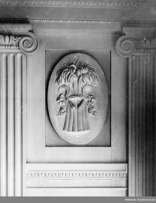 """I en tablett, en stående oval relief med emblemet """"vase med skära"""", placerad ovanför årstids-gipsfiguren """"Sommaren"""" av Gioacchino Frulli (1766-1801). Denna sitter på sydöstra väggen i stora salongen på Gunnebo slott."""