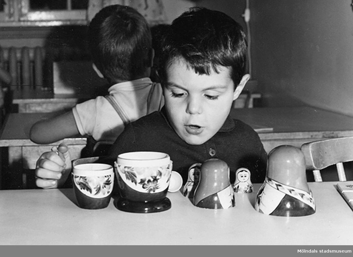 En pojke som leker med en rysk docka vid Holtermanska daghemmet 1953.