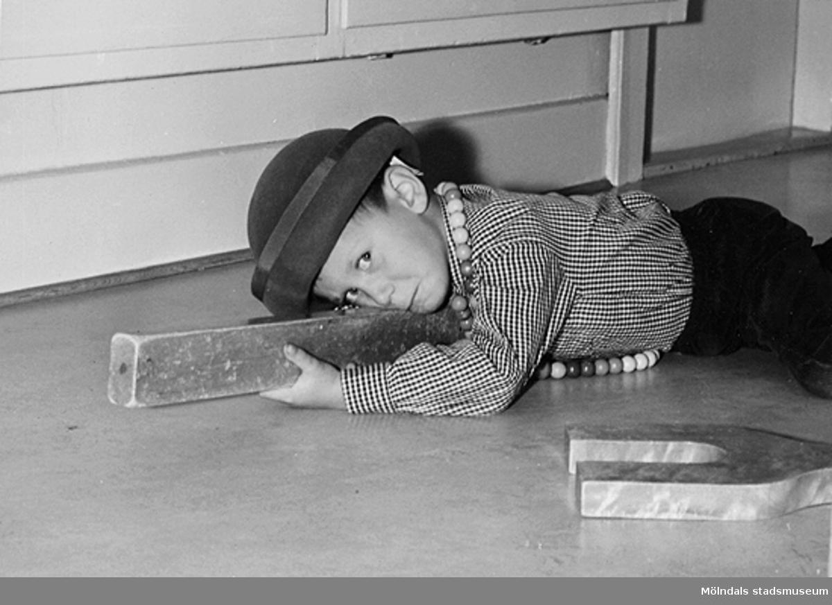 En pojke, iklädd hatt, leker med träklossar på golvet vid Holtermanska daghemmet 1953.