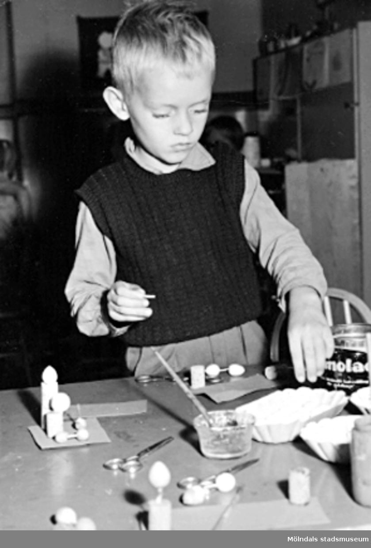 En pojke pysslar vid ett bord. Holtermanska daghemmet 1953.