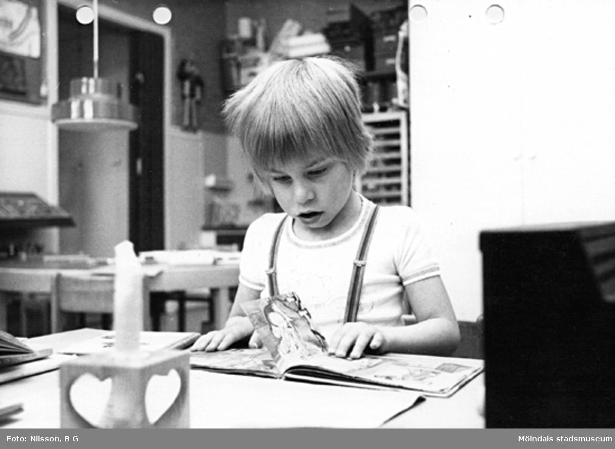 Ett barn som tittar i en bilderbok. Holtermanska daghemmet maj 1975.