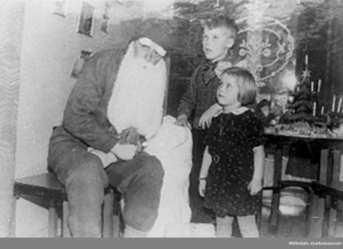"""Över fotot i albumet står """"1937"""" och under Tomte-Far """"Karl"""". Karl var tomte hos sin chef, Sven Johansson under många jular. Bilden är tagen vid ett sånt tillfälle. Med på bilden är Svens dotter och son. Dottern heter Ingrid."""