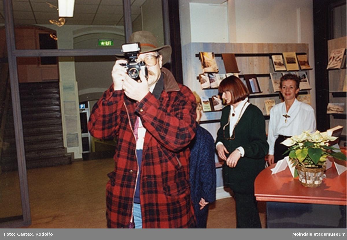 """Mölndals museum; pressvisningen av utställningen """"KW Gullers Bildminnen"""", 1993-12-10. En proträttbild på Kjell Arvidsson (chefredaktör) och hans kamera. I bakgrunden Astrid Garthman, Mari-Louise Olsson och Pia Persson."""