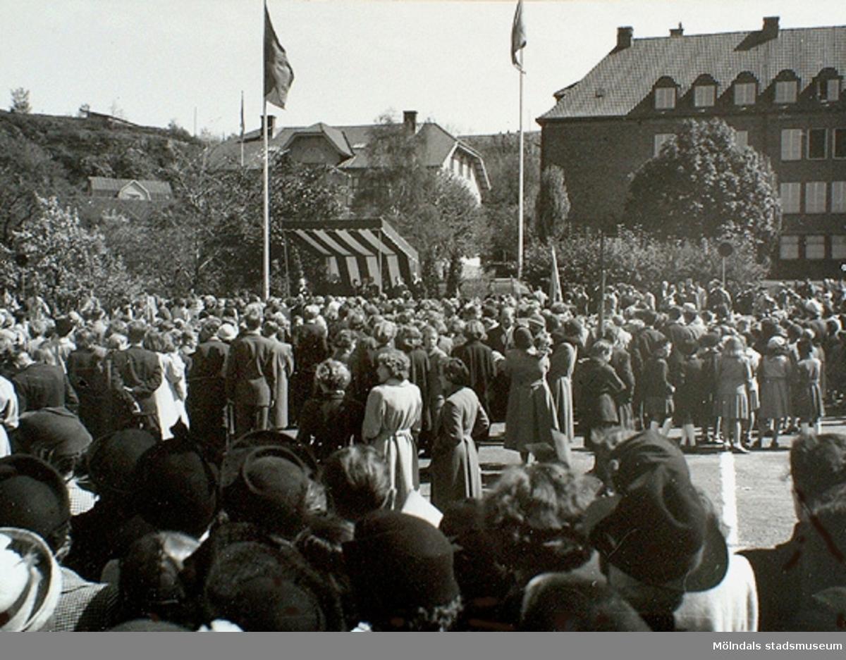 Människor har samlats på Nya torget för att se kung Gustaf VI Adolf vid invigningen av Gunnebo slott den 16 maj 1952 i Mölndals centrum. Till höger ses Kvarnbyskolan.