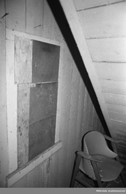 Möjligt förråd med ett igenspikat fönster och en stol i fabriksbyggnad.