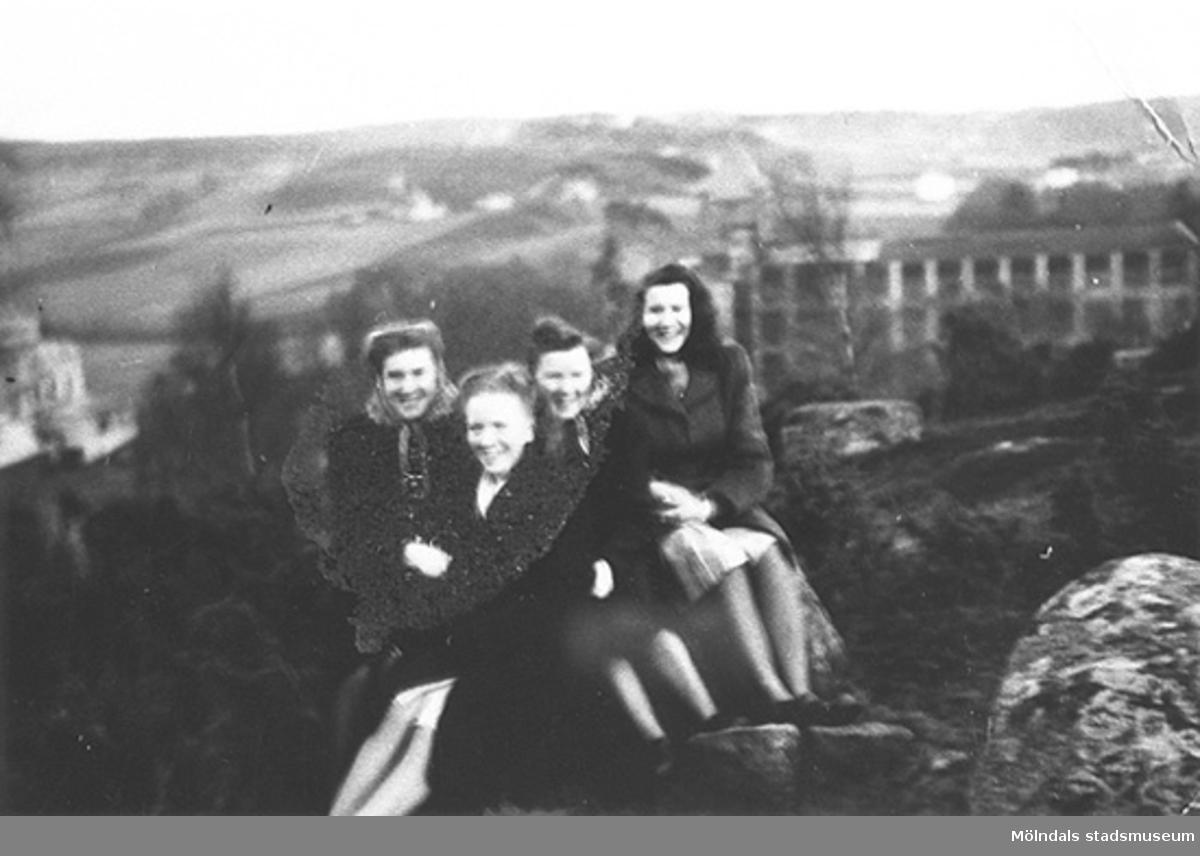 """I bakgrunden syns August Werners fabrik där de unga kvinnorna fick arbete. Hösten 1944 flydde 32.000 estländare från kriget i Estland till Sverige. Ett sextiotal personer tog jobb på August Werners textilfabrik i Lindome. Kvinnorna arbetade i spinneriet och männen i färgeriet.Mer information finns i uppsatsen """"Estländska textilarbetare i Lindome"""" som finns i Mölndals stadsmuseums interna arkiv."""
