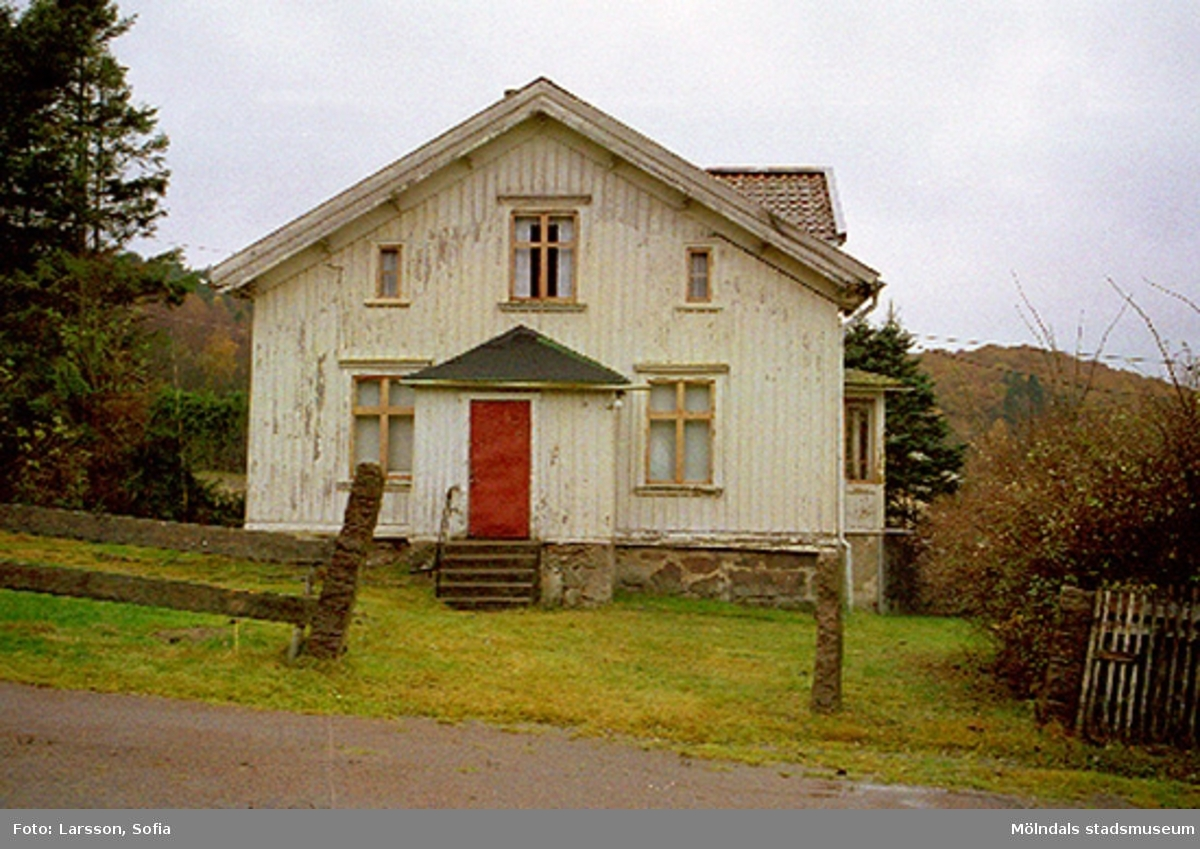 En vit färgnött villa med röd dörr och beiga fönsterkarmar. Rivningsdokumentation.