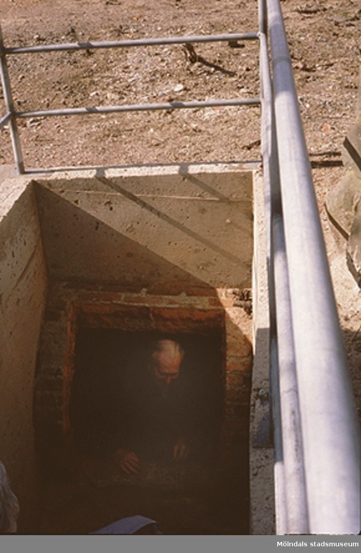"""Sven Olof Olsson kommer upp ur underjorden från ingången till det som en gång var syratornet """"Sodom"""", april 1993. På 1870-talet byggdes syratornet """"Sodom"""" strax intill Royens gata och innanför Franckegatan. Där tillverkades svavelsyrlighet som leddes i blyrör ner till Stora Götafors. Där framställdes pappersmassa enligt sulfitmetoden. I Rosendahls fabriker (pappersbruket) gjordes sedan papper. Syrligheten var starkt frätande. Blyrören lades därför i en kulvert med tegelvalv och nedgångshål, så att rören lättare skulle kunna ses över. """"Sodoms torn"""" är rivet och kulverten har inte varit i bruk sedan dess. För att man ska kunna se in i kulverten gjorde Gatukontorets parkavdelning 1992 i ordning kulverten och dess trappa. Relaterat motiv: 2003_0358."""