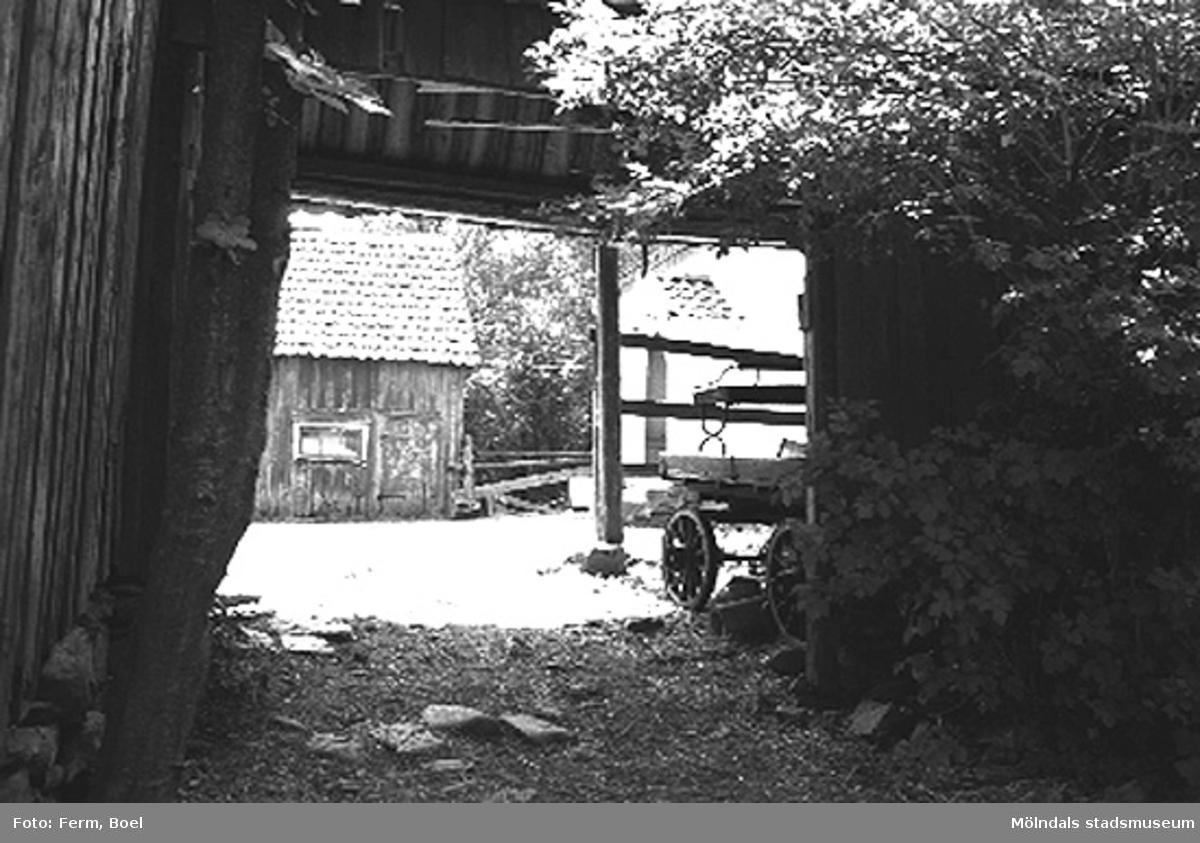 Ett portlider som leder in till en stensatt gårdsplan.Högen 2:1/2:2 i Kållered, 1992-06-30.