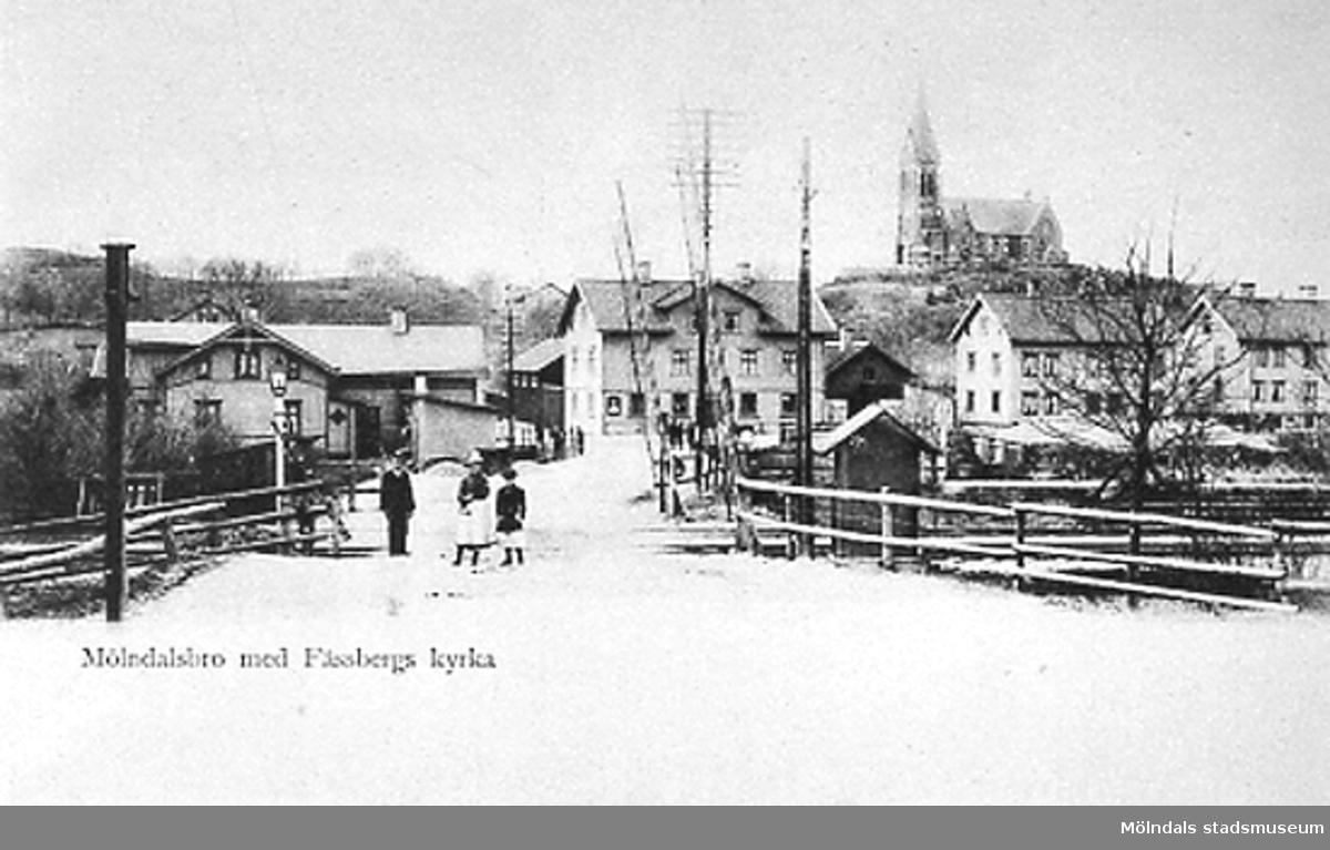 Kvarnbygatan vid Hallandsbanan med Mölndalsbro och Fässbergs kyrka i bakgrunden. Man ser järnvägsövergången på Kvarnbygatan och fastigheterna Kungsbackavägen 1, samt Göteborgsvägen 1-3 och 5. Vid vänstra gaveln av Göteborgsvägen 1 ses Villa Björkås, Frölundagatan 25B. Spårvagnshallarna är inte byggda, fotot är taget innan 1907.