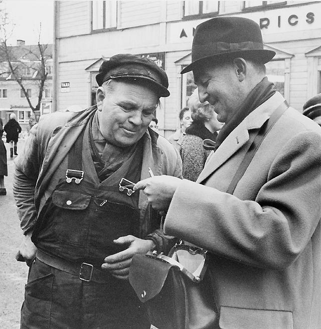 Många händer - här bl a Sten Johanssons, Trosa - gick villigt till plånboksfickan när Trosas innevånare mötte konstnär Reinhold Ljunggren med konduktörsväskan på magen. Han gav sig ut bland vänner och bekanta och sålde postens helgkort på löpande band.