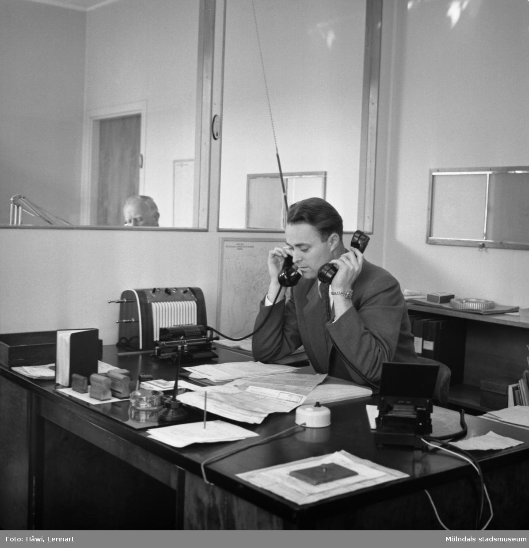 En man vid ett skrivbord i ett kontor talar i Papyrus kommunikationsradio. Mölndal, 12/9 1956.