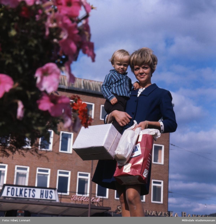Kvinna med pojke i famnen fotograferade vid Stadshusplatsen i Mölndal, 17/9 1968.