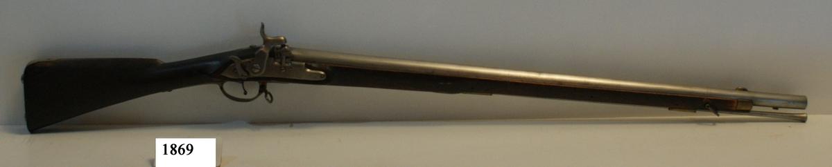 """Gevär,  försöks-, 1831 års modell, typ a, för flottan, ändrat från flint- till slaglås (säkring med fällbom). Märkt: """"6"""". Kolven av trä, pipa och mekanism av stål. Beslagen av metall. Pipan slätborrad, längd 857 mm. Stickbajonett, längd 700 mm. Kaliber: 19 mm. Vikt: 3,9 kg. Hela längden: 1260 mm."""