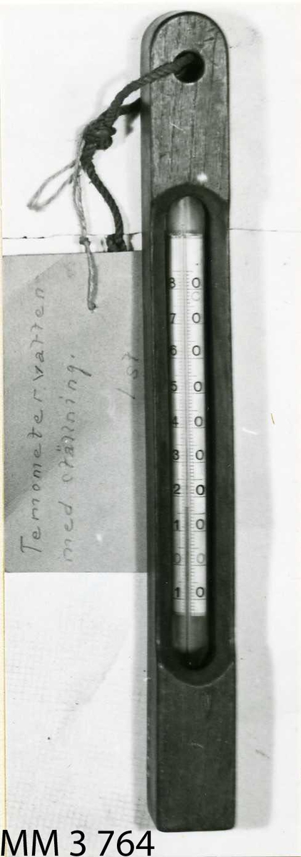 Termometer, av glas och kvicksilver, i ställning av trä, graderad -50 + 120 grader C. Termometern cylindrisk.