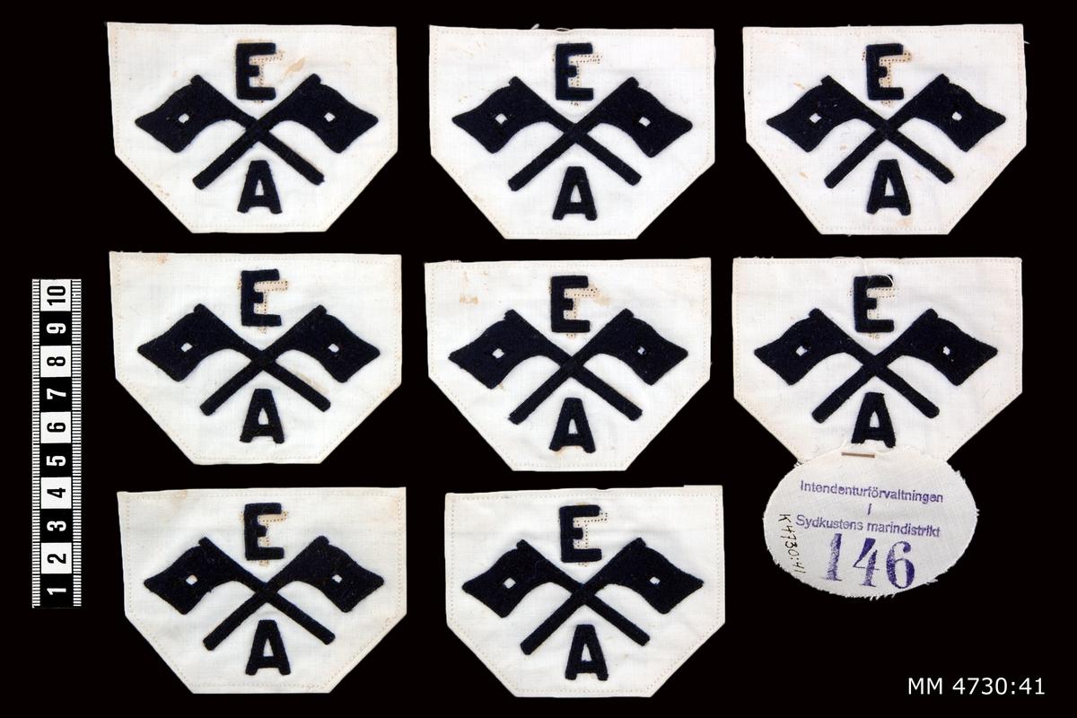Yrkesbeteckning, signalflaggor med E och A, M/26. Av blått kläde på vit botten. För eldledningsman och avståndsobservatör. 9 stycken.