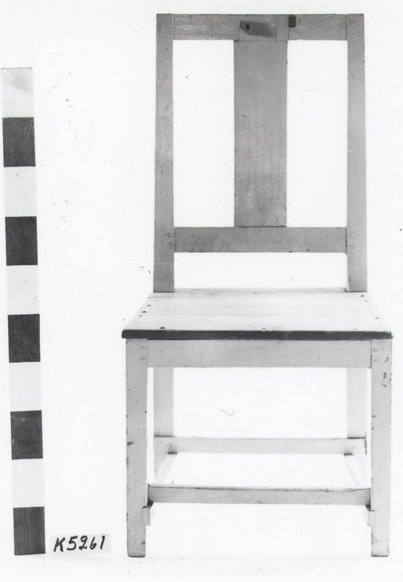 Stol av furu, vit- och gråmålad. Större. Rak modell med raka fyrsidiga ben samt rektangulär ryggbricka. Märkning: 1826.
