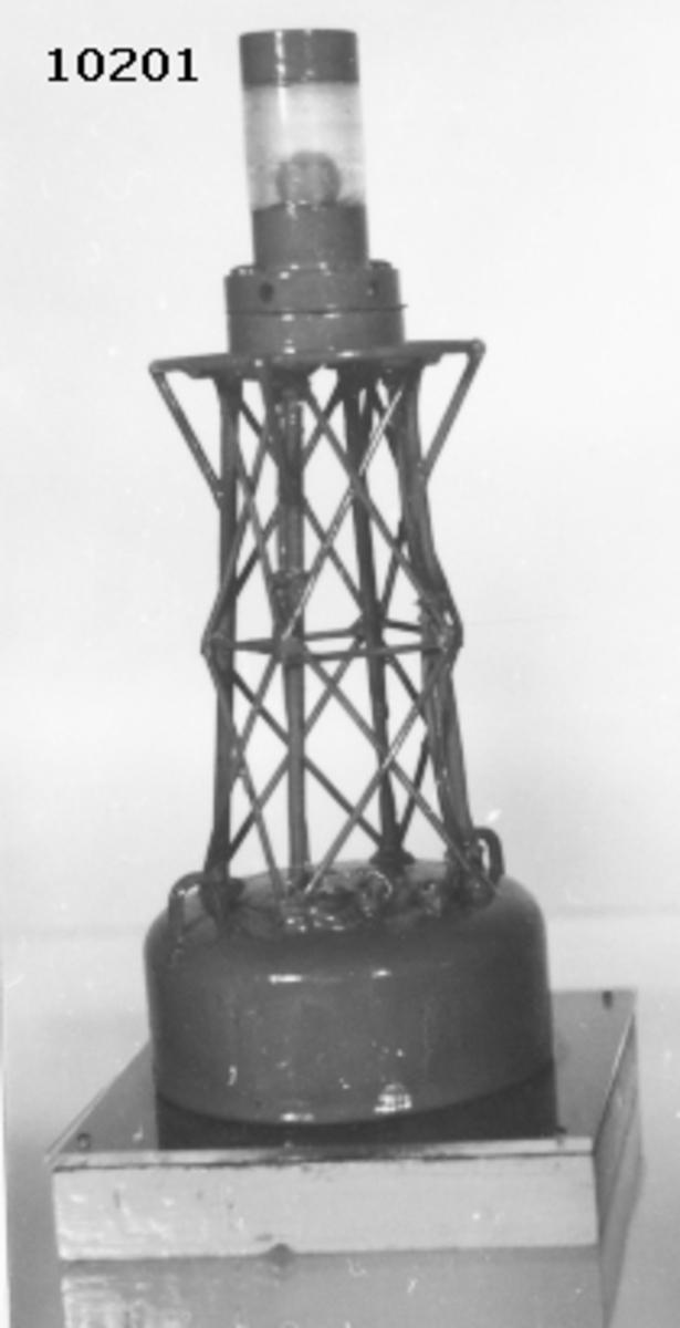 Modell av lysboj. Består nederst av en cylinder av trä med stativ av järntråd, i toppen lamhålare med el-lampa, skyddad av ett cylindriskt glas. Svartmålad. Bojen är monterad på en träplatta, botten och sidorna är ljusgrå, översidan blå, täckt av ett plexiglas.