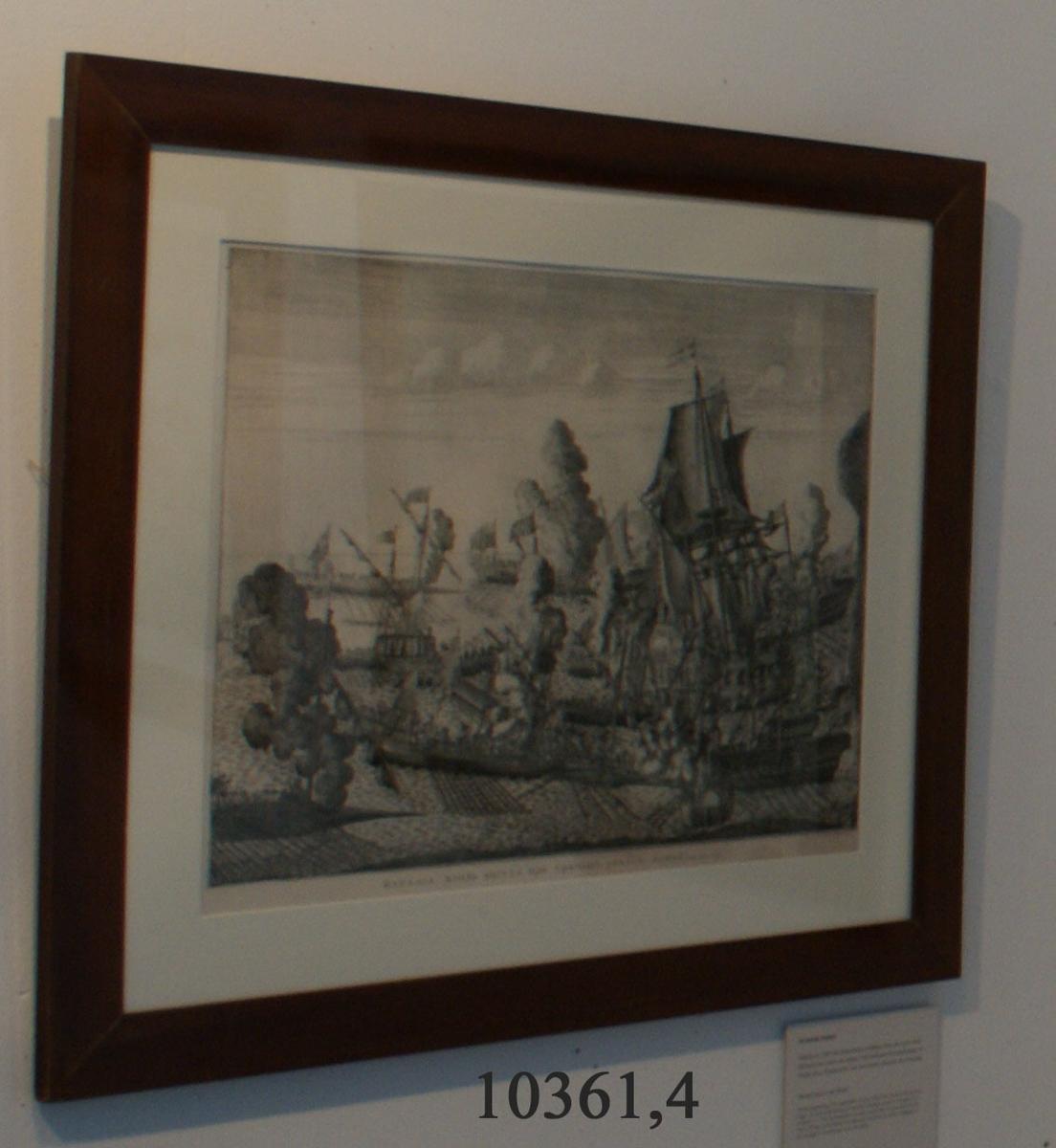 """Kopparstick, liggande format, visande sjöstrid mellan svenska och ryska flottan; ryska galärer omringar svenskt linjeskepp, totalt ett 15-tal fartyg i bild. Mot högra sidan av bildytan syns kanterna av ett berg i förgrunden. Nedanför bilden rysk text som avslutas med """"1714"""" och """"23"""". I högre, nedre hörn förmodligen konstnärens eller gravörens namn samt år """"1715"""". Kopparsticket är ramat i brun slät mahognyram med guldkant närmast motivet samt glas."""