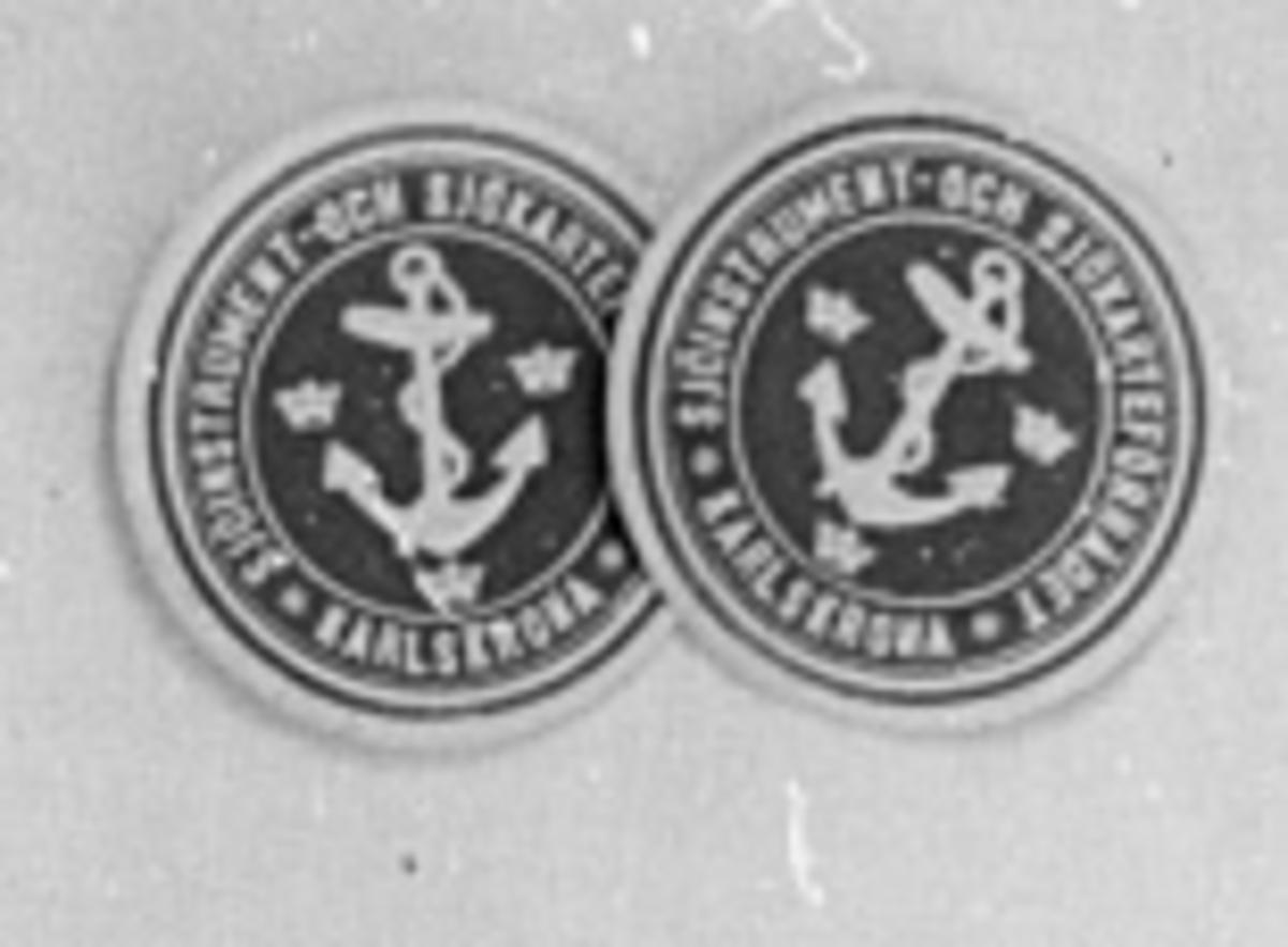 Munlack cirkelrund pappersbit med blå ovansida med figur och text i vitt. I mitten et ankare och tre kronor. Runt ankaret texten i vitt: Sjöinstrument- och sjökarteförrådet, Karlskrona. Baksidan gummerad.