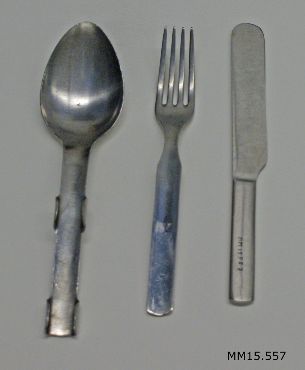 Matbestick av rostfritt stål. Sked, gaffel och kniv som hållas samman genom dom flikar, som finns på skedens skaft. Besticket är avsett att användas i fält.