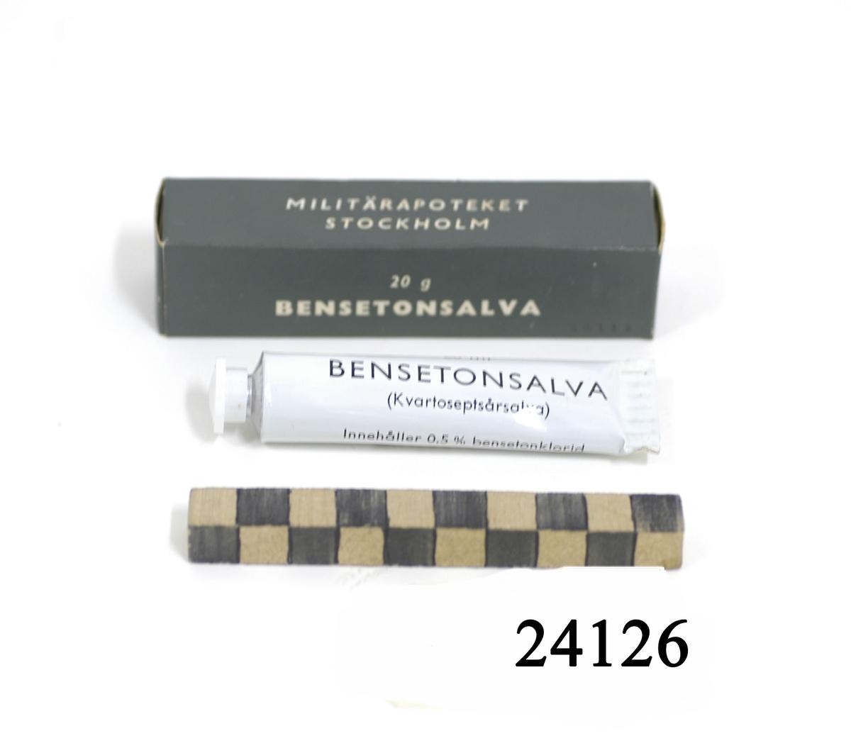 """Vit tub av metall, vit skruvkork av plast. På tuben svart text: """" 20 ml Bensetonsalva ( Kvartoseptsårsalva ) Innehåller 0,5 % bensetonklorid. MILITÄRAPOTEKET STOCKHOLM """". Tuben förvaras i mörkgrön pappersförpackning med vit text: """" 20 g BENSETONSALVA. MILITÄRAPOTEKET STOCKHOLM , 66111 """"."""