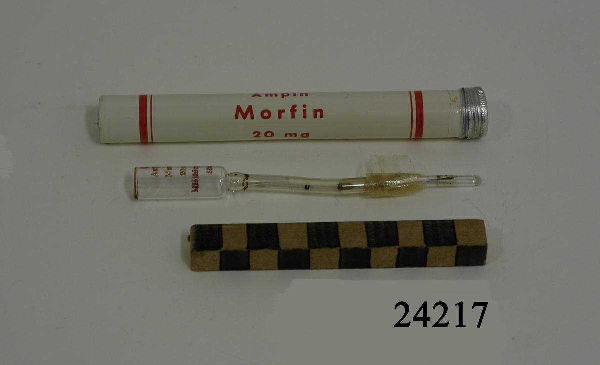 """Smalt vitt rör av metall med skruvlock av vit metall. Röd text: """"Ampin Morfin 20 mg, Morfinampinen användes vid mycket svåra smärtor enligt inneliggande bruksanvisning. Obs. Vid smärtor i buken får morfin icke givas. Militärapoteket, Stockholm"""". Röret innehåller bruksanvisning samt en ampull med kanyl. Ampullen innehåller ej läkemedel."""