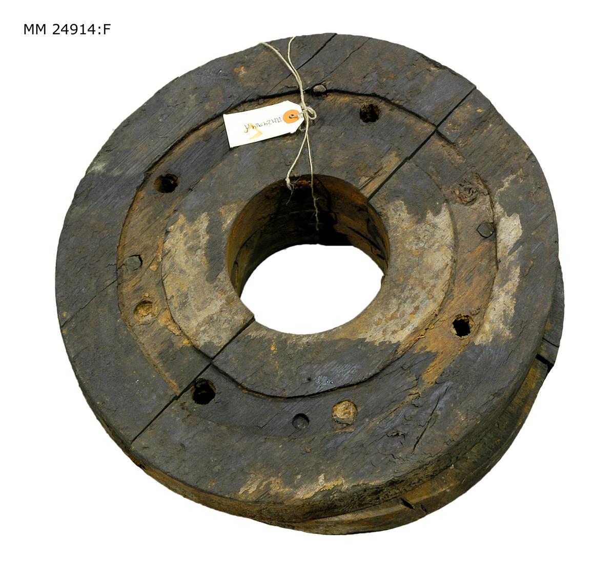 Svart hjul som består av flera hopsatta delar som hålls samman av en järnring. Hål i mitten för hjulaxeln.