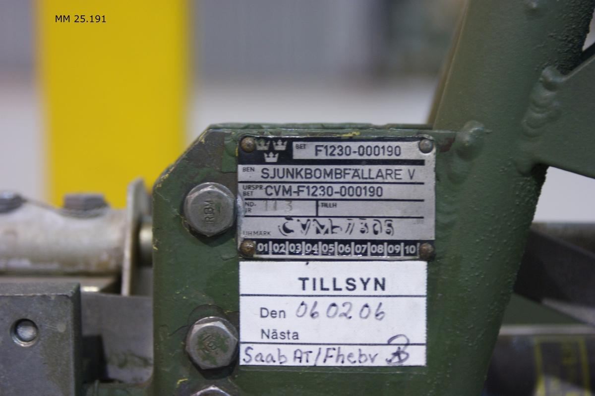 """Grönmålad metallställning av sammansvetsade rör med plats för tre sjunkbomber. I toppen sitter fällningsanordningar märkta B, A och C samt förseddamed heraldiskt vapen som utgörs av marinflygets märke i blått på gul botten med kungakrona. Varje fällningsanordning har en grön del och metallfärgad del. Den metallfärgade delen märkt: """"US Navy Bu. Of. Ord. Bomb schackle. Mark 8 Mod 4"""" med mera. Kablar går till varje fällningsanordning. Märkningar med gula dymoremsor: """"13.2"""". På en metallbricka anges materielnummer F1230-000190 och individnummet 113."""