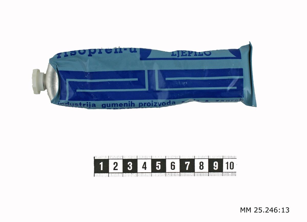 Ljusblå klistertub med vit, oktagonformad skruvkork. Text på tuben i mörkblått anger produktionfomation och tillverkare på slaviskt språk, sannolikt kroatiska.