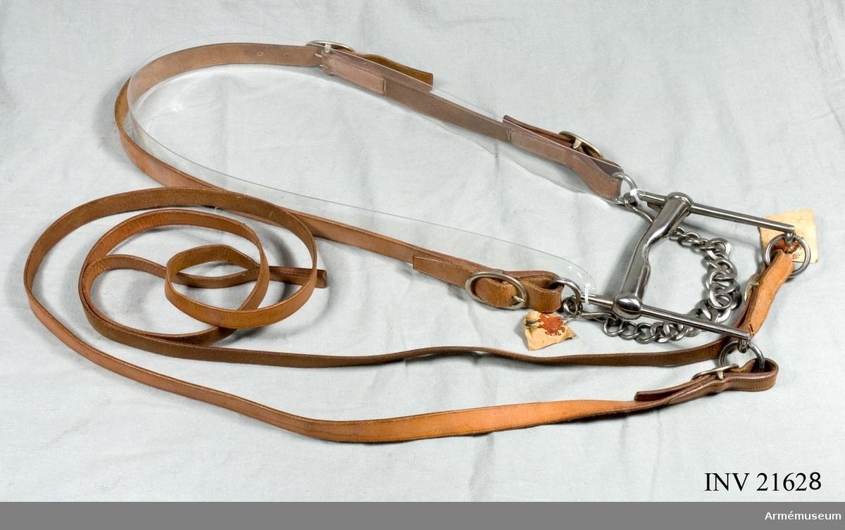Samhörande gåva: 21628 stångbetsel, 21629 bridong. Grupp C I. Ingår i fältkandar m/1890 för officershäst vid kavalleriet. Hela  betslet består av stångbetsel och bridonggrimma. Modellexemplar.Stångbetslet består av huvudlag, stångbett och stångtyglar. 1. Huvudlag har två sidstycken, b:25 mm, spända genom en 50 mm  lång, oval sölja på sidstyckets vänstra sida. Båda sidstyckena  har också en 50 mm lång, oval sölja för att spännas ihop vid  stångbettet. 2. Stångbett m/1890 är 120 mm brett, utbockat och med fast  mellanstycke. Sidstängerna är raka och 170 mm långa. Tygelringar  med diameter 35 mm och 55 mm långa krokar. Lös kindkedja. Kindkedjan saknas. 3. Stångtyglar, b:18-20 mm, som är hopsydda med ändarna bredvid  varandra, spända samman genom 40 mm långa, ovala söljor vid  tygelringarna.
