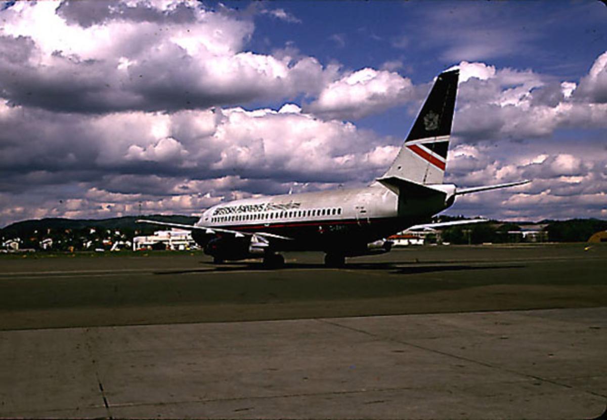 Lufthavn, 1 fly på bakken, Boeing 737 200, Titania, G-BKYL fra British Airways, skrått bakfra. Noe av flyplassbygningene i bakgrunnen.