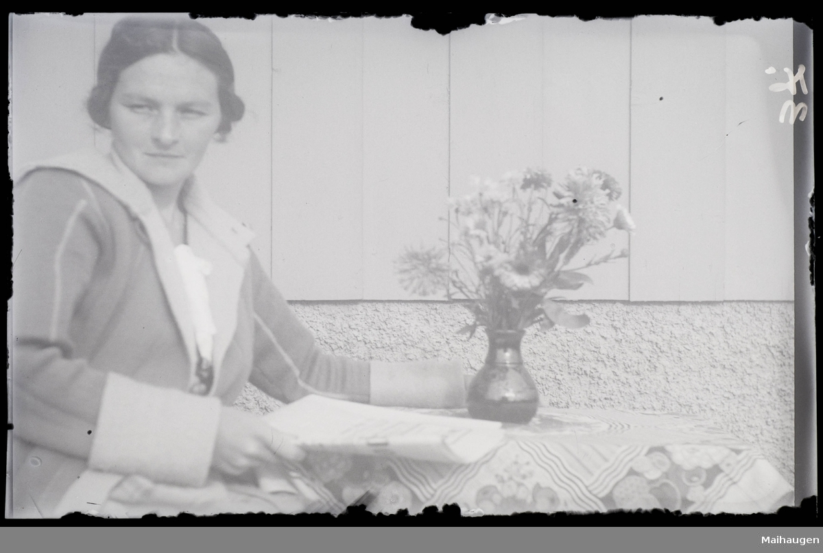 Kvinne på veranda. Vase med blomster.
