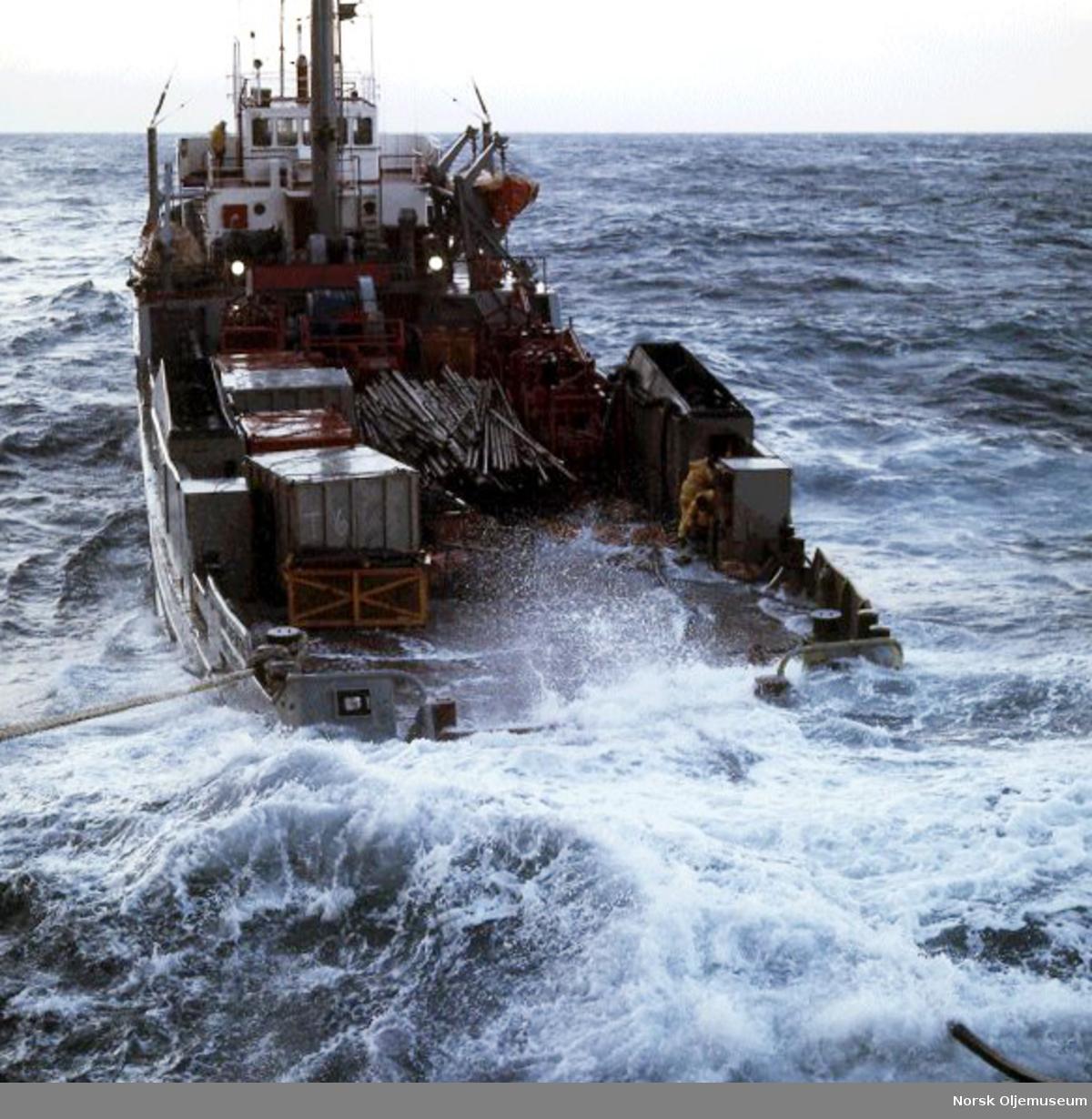 """Supplybåten """"Holstentor"""" i store bølger. Mannskapet jobber mens bølgene slår over dekk."""