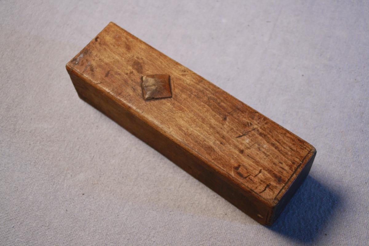 Bearbeida trestykke med. Den sida som har vore øvst har ein utskoren firkant. Undersida er ikkje beisa som resten av trestykket. Ukjend kva den har vorte nytte til. Vart funnen saman med snekkarutstyr. Låg i kiste KSF.000227.