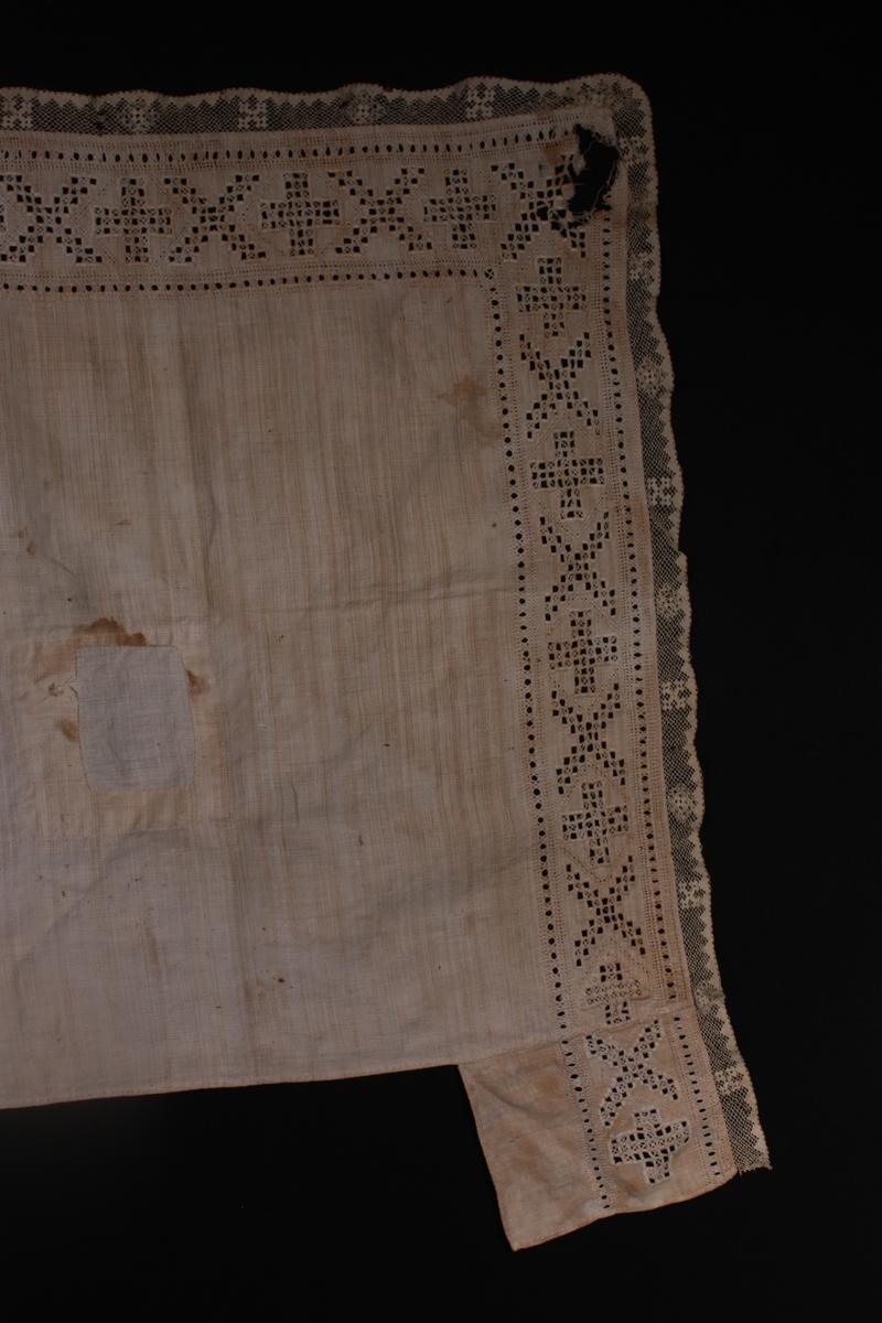 Kvadratisk med kvitsaum på to sider. Påsydde lappar med same broderte mønster i kvar ende av broderiet. Filert blondekant. Lappa i midten.