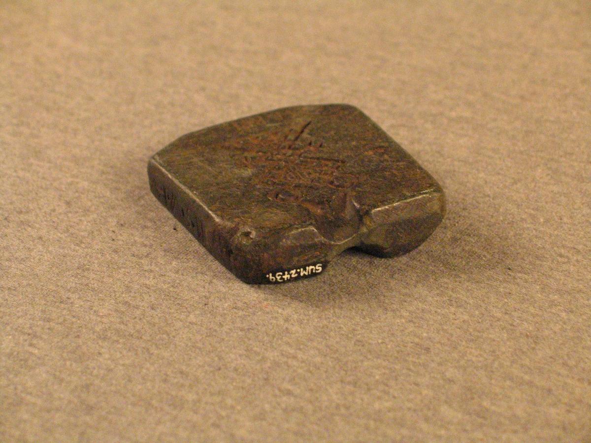 Rektangulær klebersteinsform med inngravert støypeform til maljer på begge sidene. Maljene er like i form, men ulike i storleik.