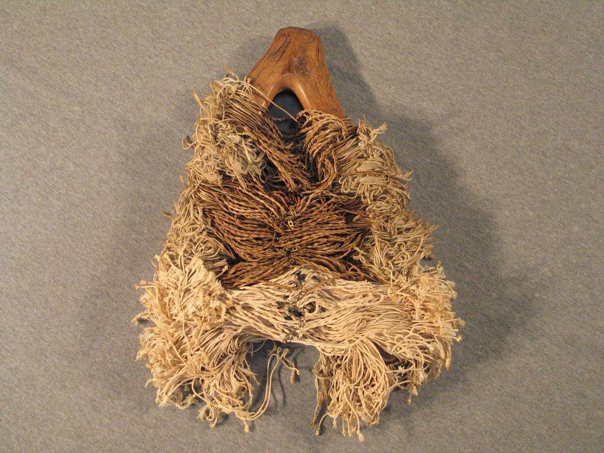 Naturvaksen v-forma krok. På denne er det tredd mange ferdige hovlar av lin og bomull. I enden av eineI eine enden er laga hol slik at kroken kan henge på veggen, i andre henden er laga hake som hindrar hovlane i å dette av.