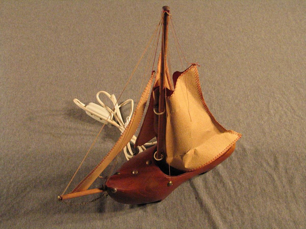 Treskobåt med full seglføring og lampe inni seglet. Teikning av seglbåtar på segla.