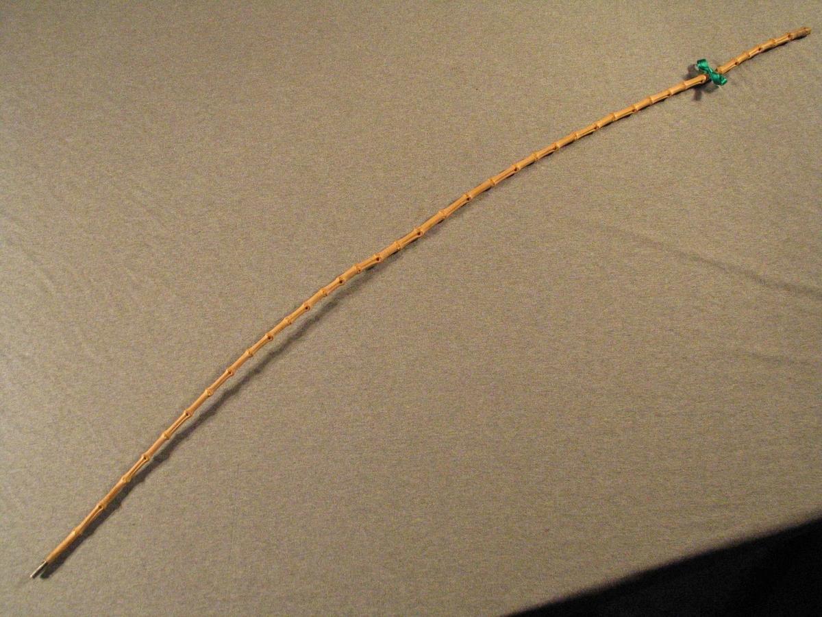 Tunn bambusstokk med metallskoning nederst. Grøn silkesløyfe knytt rundt ca. 15 cm. nede på staven.