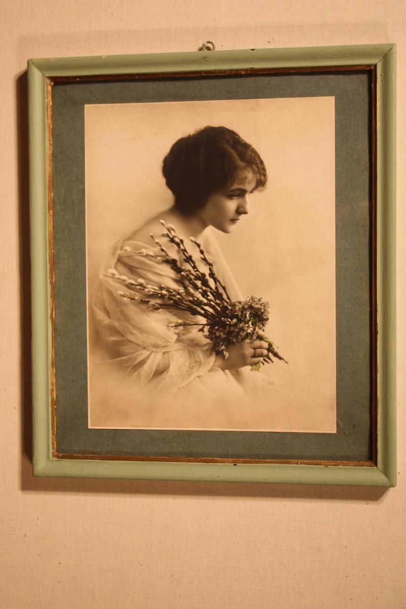Portrett av ung dame i profil. Sveipa i tunt flor, held ein bukett med gåsungar og korte blomster i høgre handa. Limt på grøn papp. Profilert treråme som er måla lys grøn med gullrand inst mot glaset. Augekrok på toppen til oppheng.