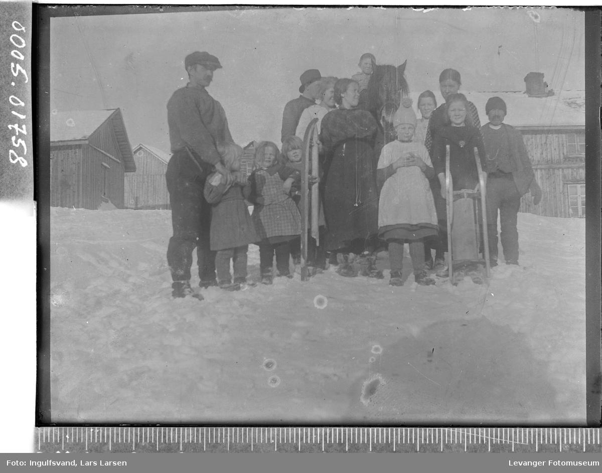 Gruppebilde av voksne, barn og en hest på et gårdstun.